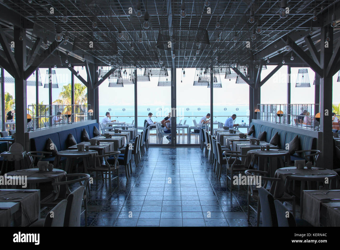 The restaurant at the five star hotel Ramada Plaza, morning, empty tables, sea view - Stock Image