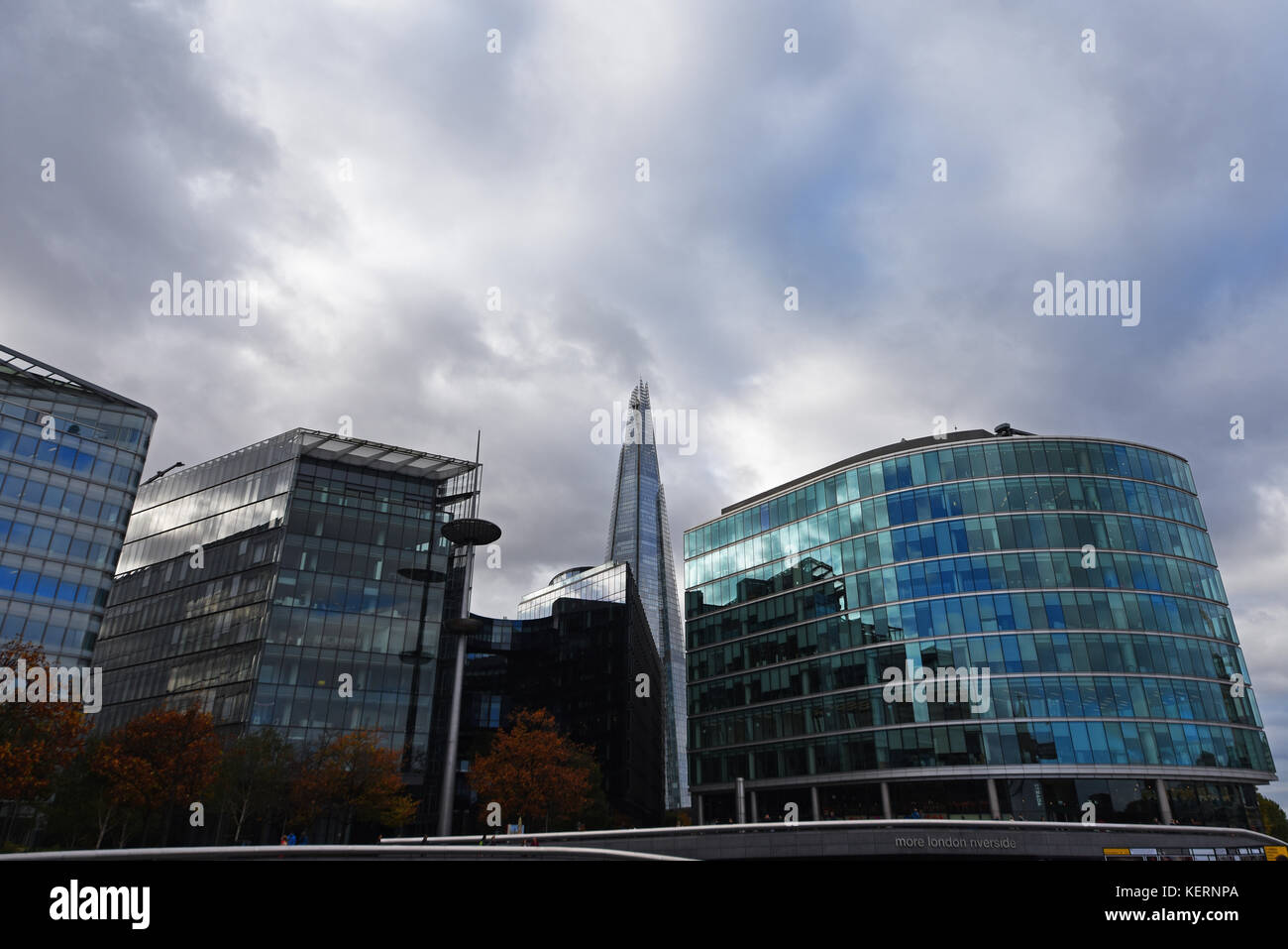 The Shard and More London Riverside buildings in autumn fall with red orange leaves on trees. Overcast and wintry. - Stock Image
