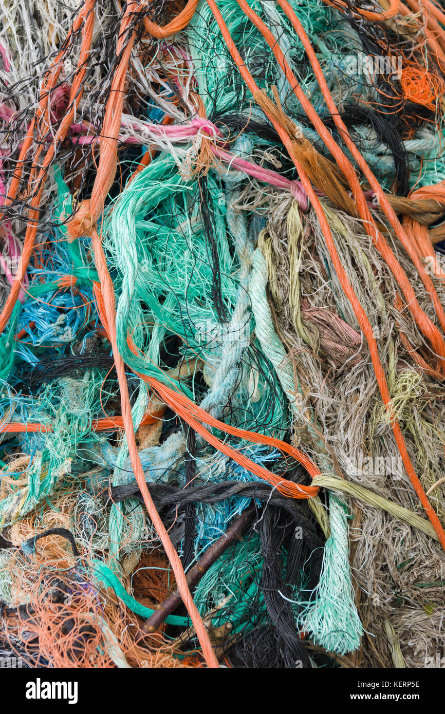 A tangled mess of fishing nets plastic rope and other debris washed up on a British coastal beach ideal for an ecological - Stock Image
