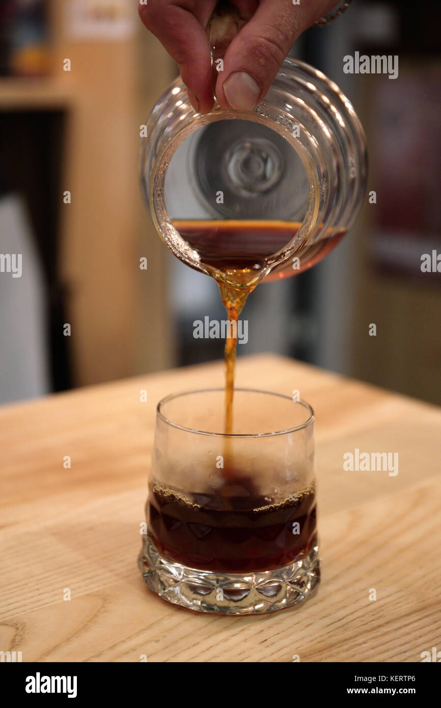Barista pours a coffin into the glass cup serves a drink. Kemex - Stock Image