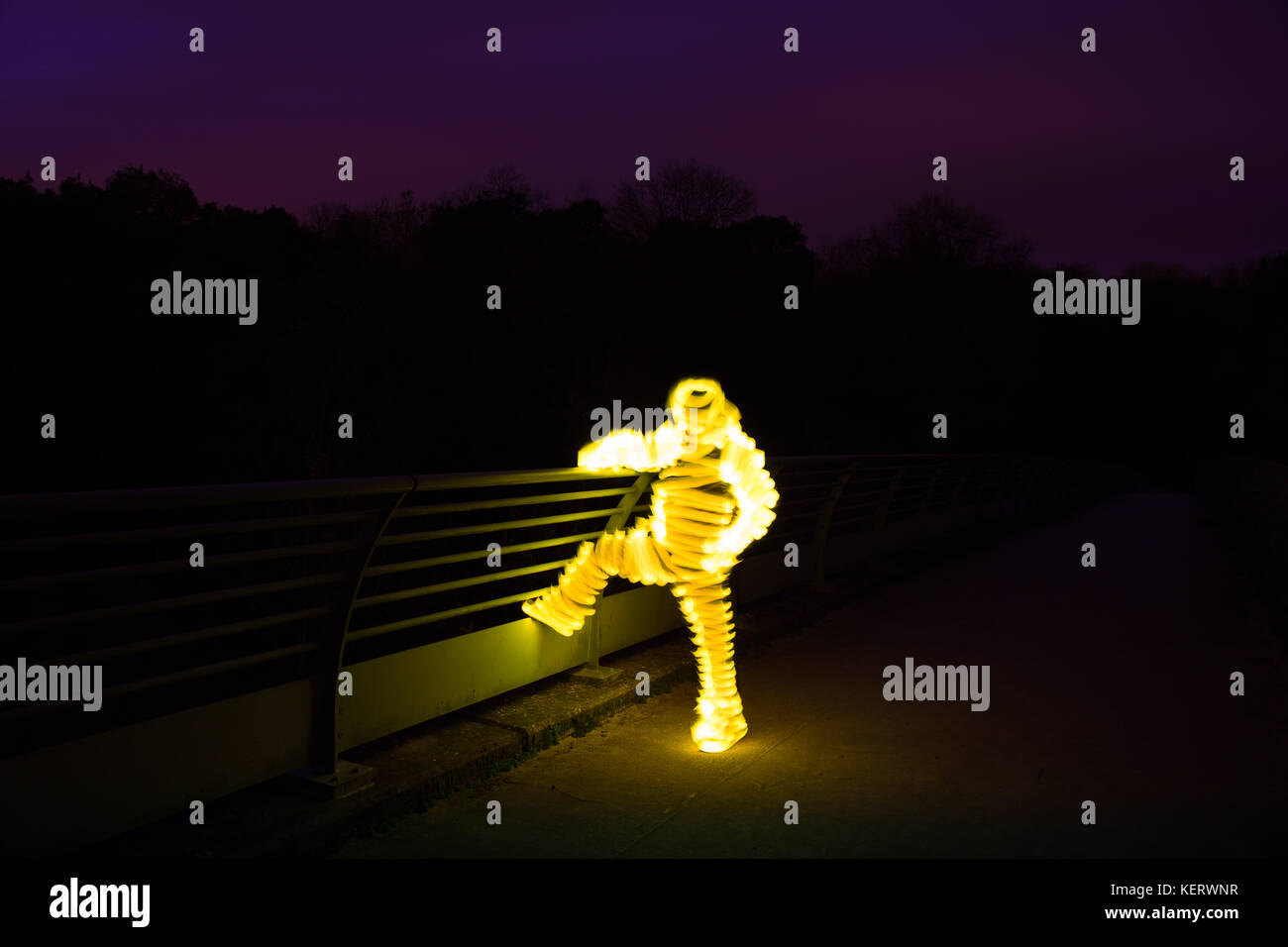An unexplained, glowing figure stands alone on a bridge in the darkness. Night scene. - Stock Image