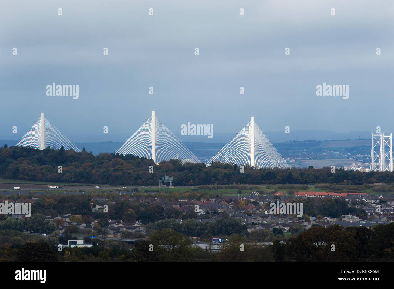 A view of the new Queensferry Crossing and Forth Road Bridge illuminated by the sunshine with Kirkliston village in foreground on a dull October day. Stock Photo