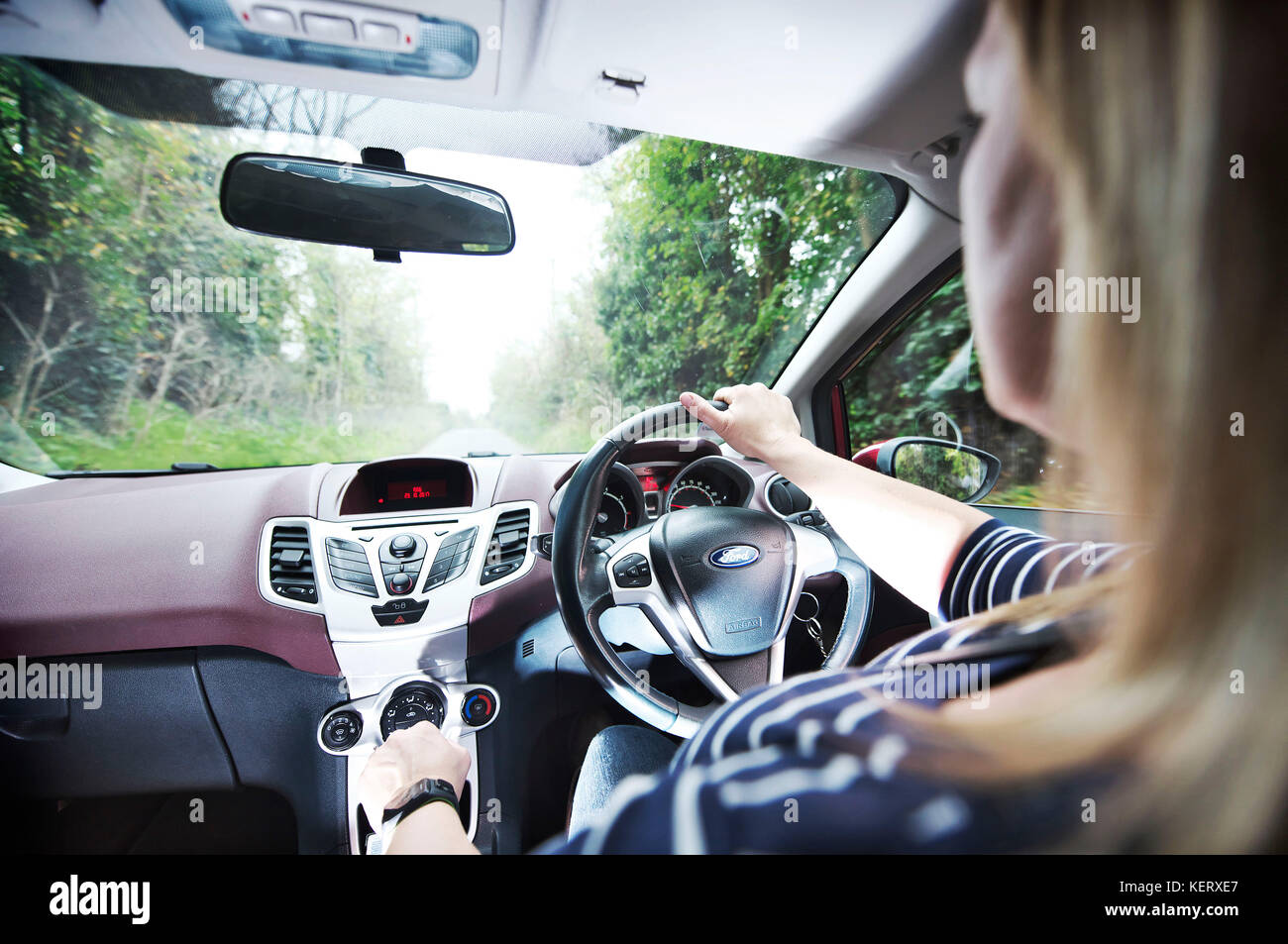 White female is driving a small car on here daily commute to work - Stock Image
