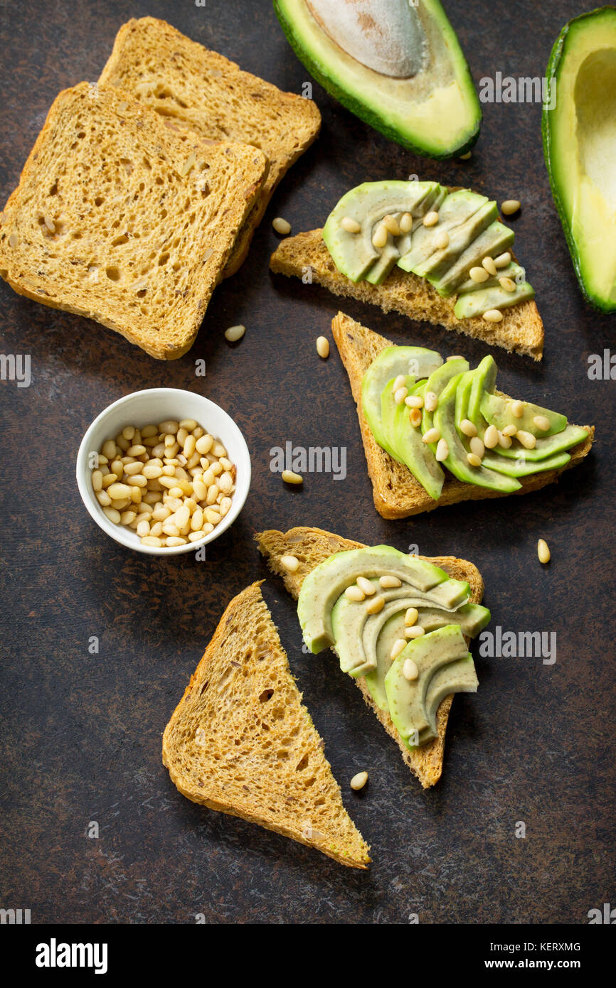 Sandwich avocado with fresh sliced avocado and pine nuts on a dark slate or stone background. Flat lay, top view. - Stock Image