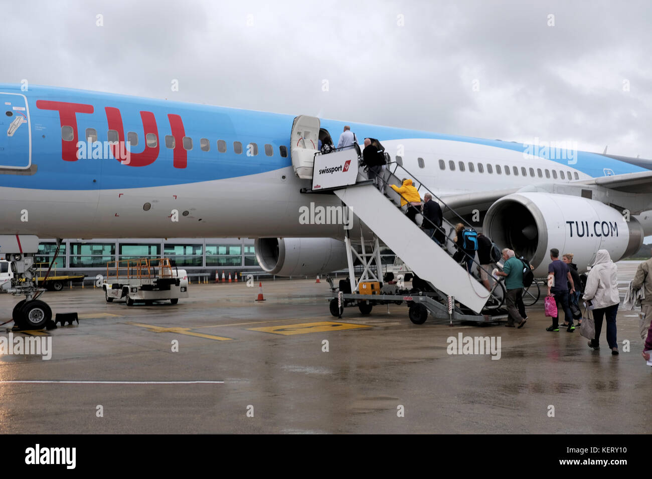 A TUI aircraft standing on the airport apron at Bristol airport in the rain. The aircraft is being boarded by passengers - Stock Image