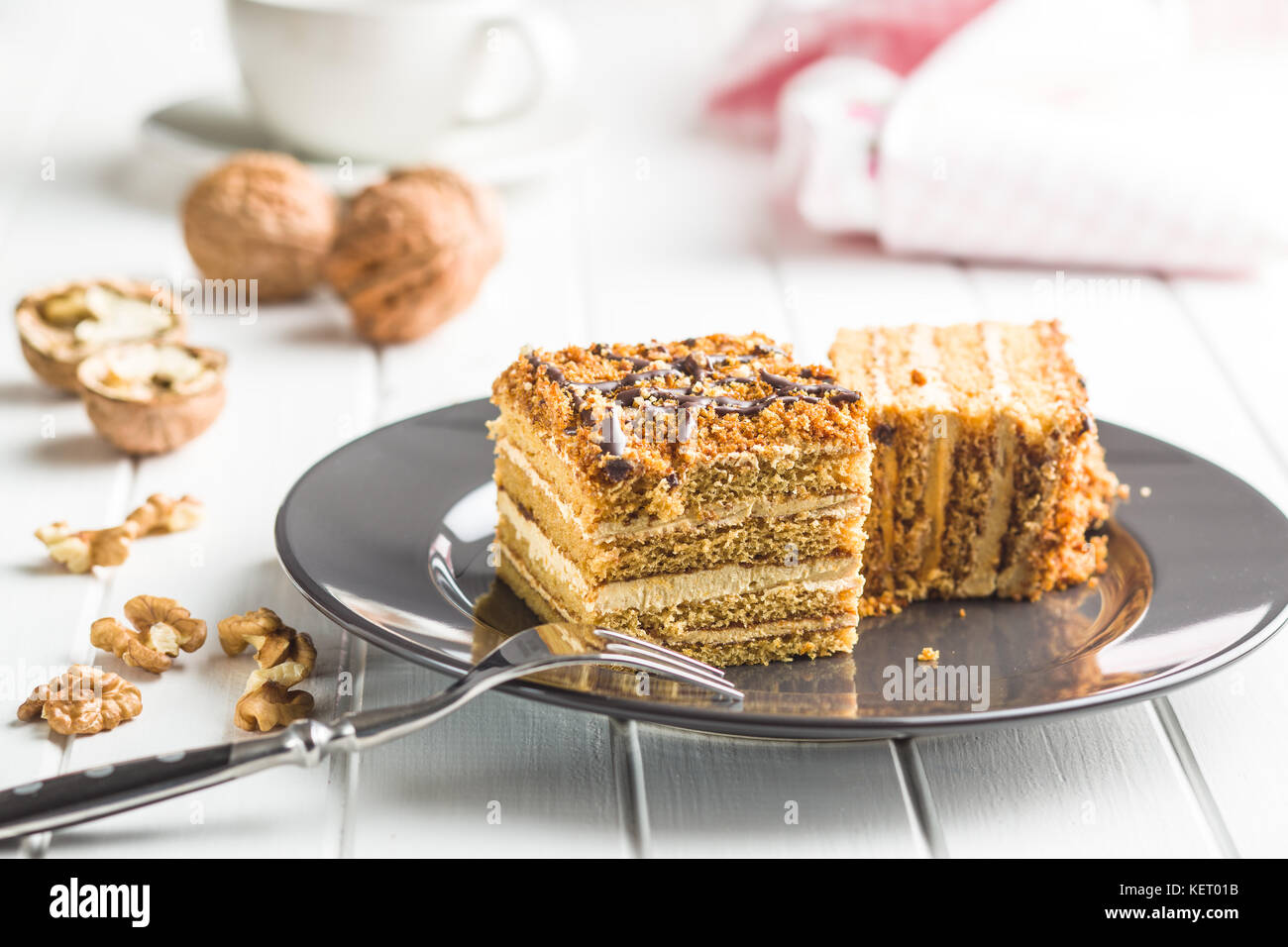 Cake with walnuts and honey on plate. - Stock Image