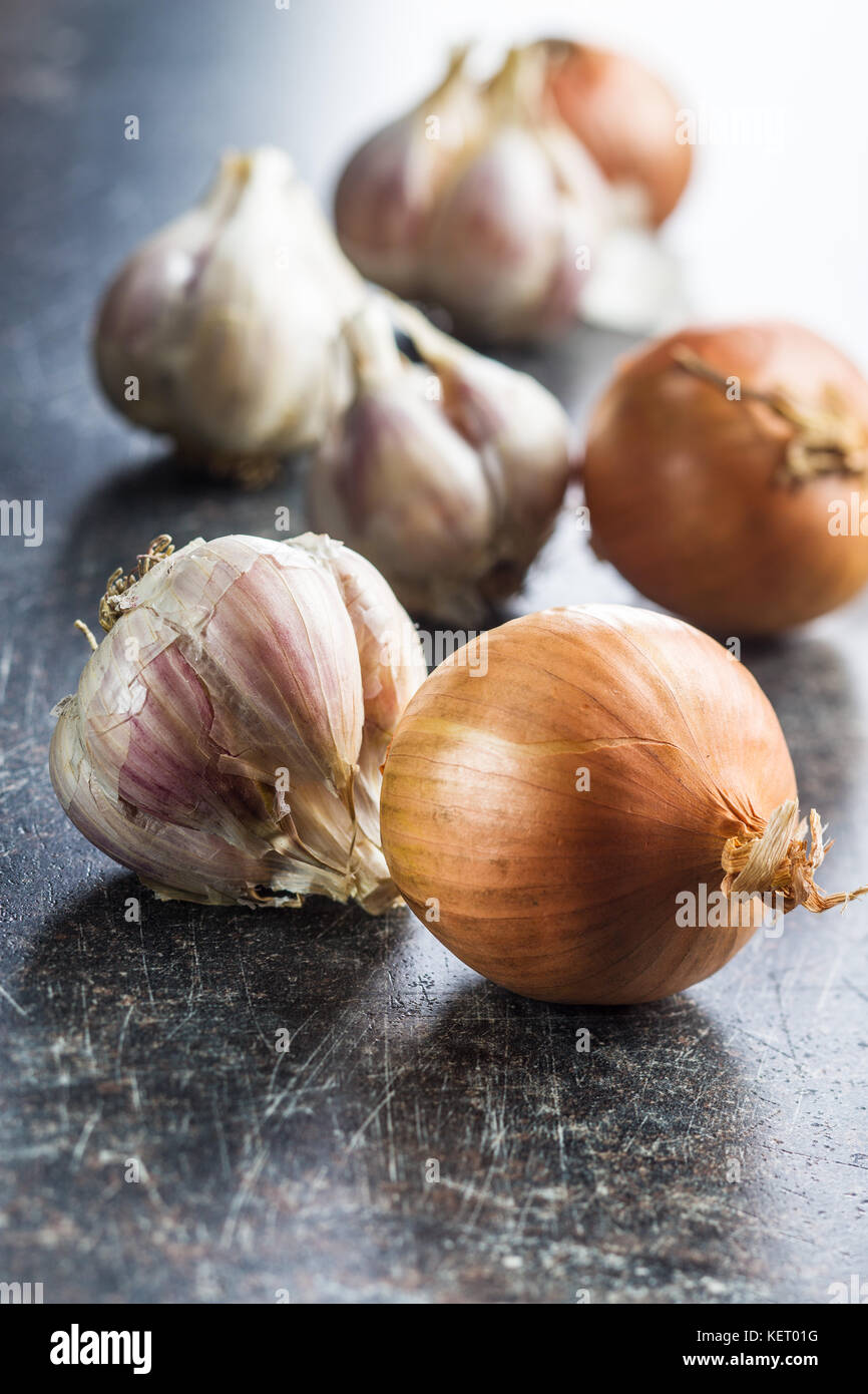 Fresh onion and garlic bulbs on old kitchen table. - Stock Image