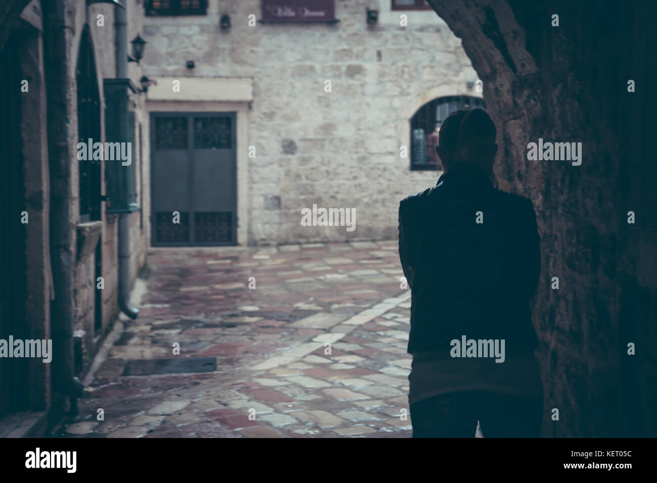 Lonely  woman silhouette walking through dark tunnel of street in rainy day in old city during rain with copy space Stock Photo