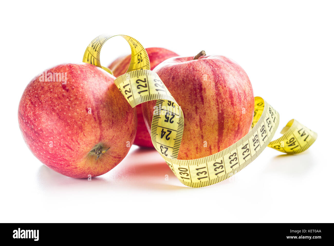 Fresh apples and measuring tape isolated on white background. - Stock Image