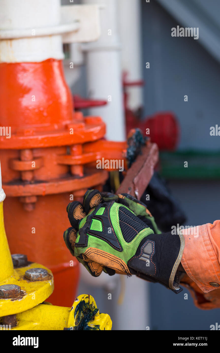 Man or able seaman is opening valve of a big pipe. Liquid Cargo  - Stock Image