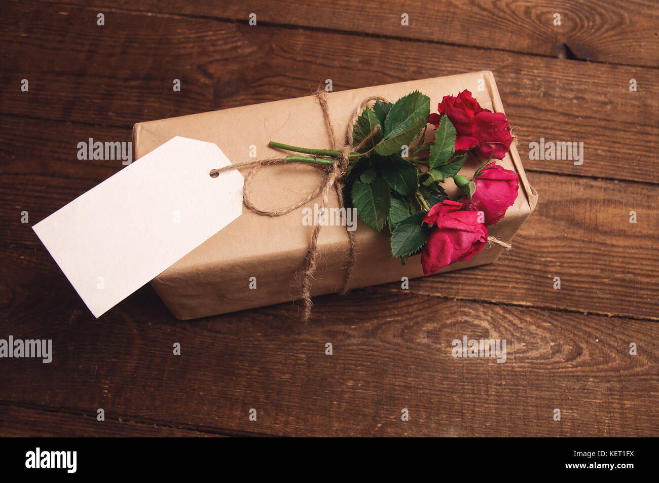 Gift Wrapped In Kraft Paper With Rose Flower On Top Stock Photo