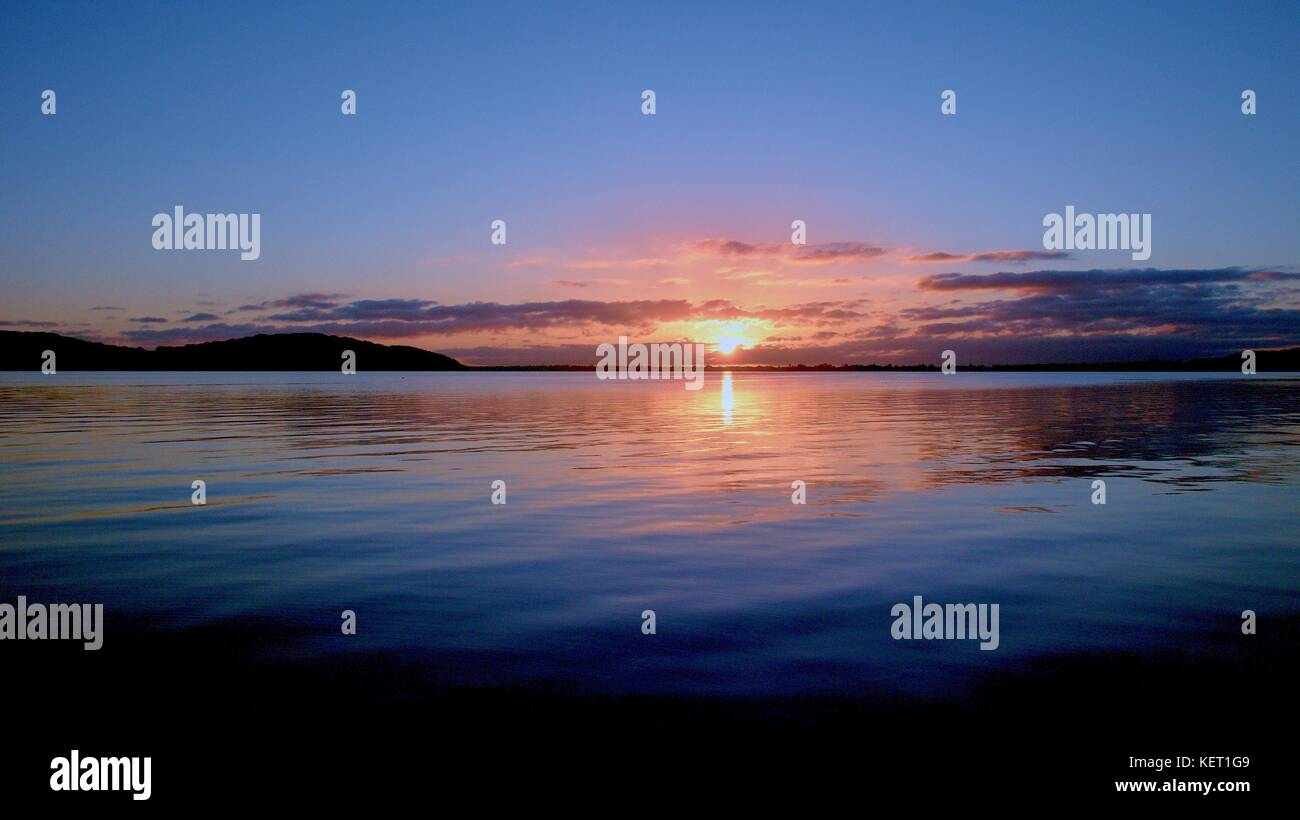 Gold and grey sunrise seascape with water reflections in the tranquil waters of Lake Macquarie at dawn. New South - Stock Image