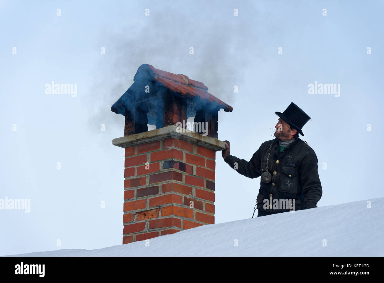 Chimney sweeper in winter on a roof with smoky chimney, Upper Bavaria, Bavaria, Germany - Stock Image