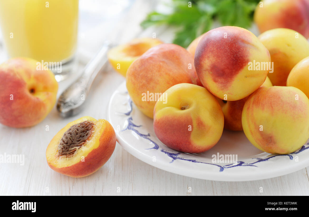 Still life with fresh ripe nectarines on white wooden table - Stock Image