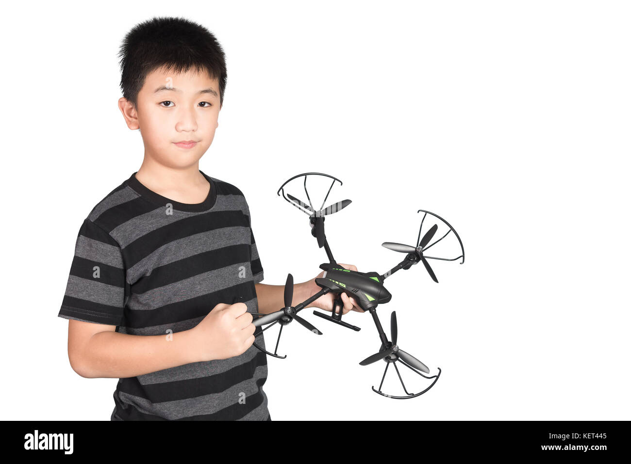 Successful happy and attractive Asian boy holding hexacopter drone and punching the air with his fist, isolated - Stock Image