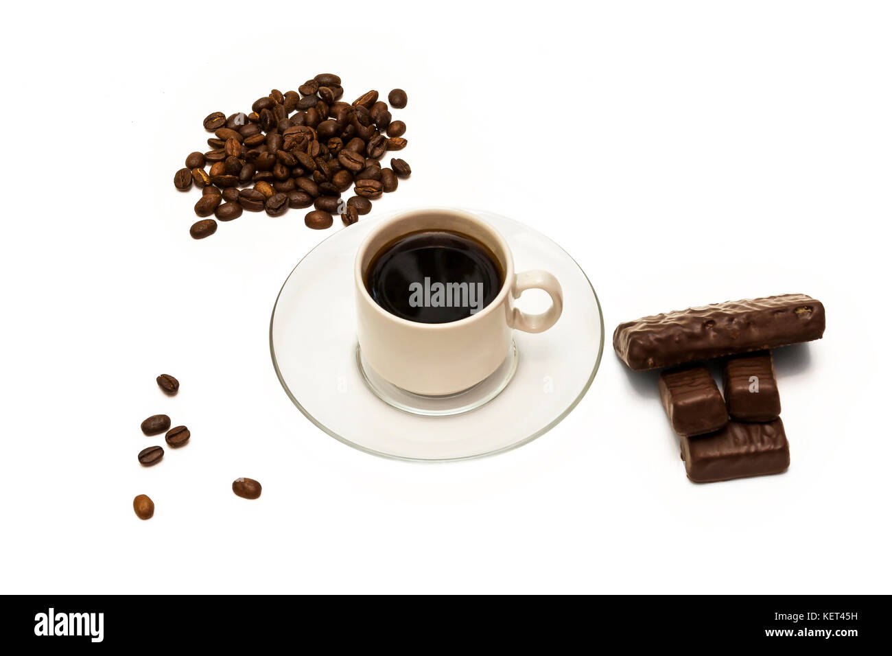 Grains of coffee, a cup of coffee and chocolate candies on a white background - Stock Image