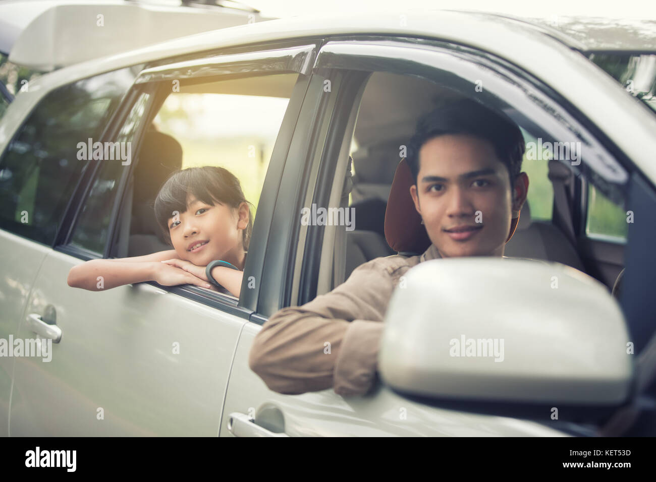 happy little girl  with asian family sitting in the car for enjoying road trip and summer vacation Stock Photo