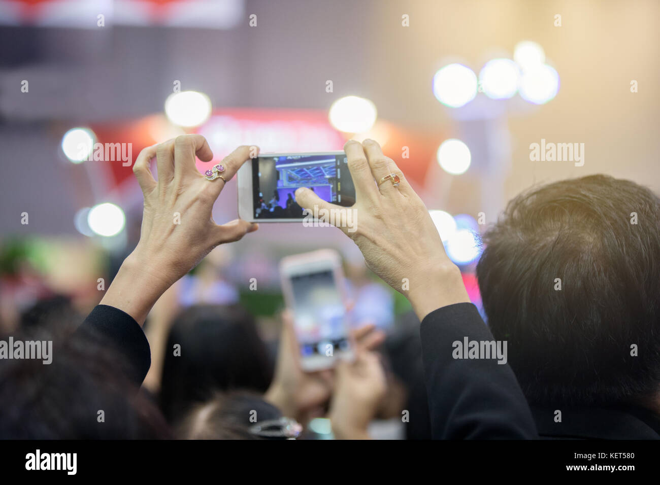 Asian old women holding smartphone and tapping screen for taking pictures. - Stock Image