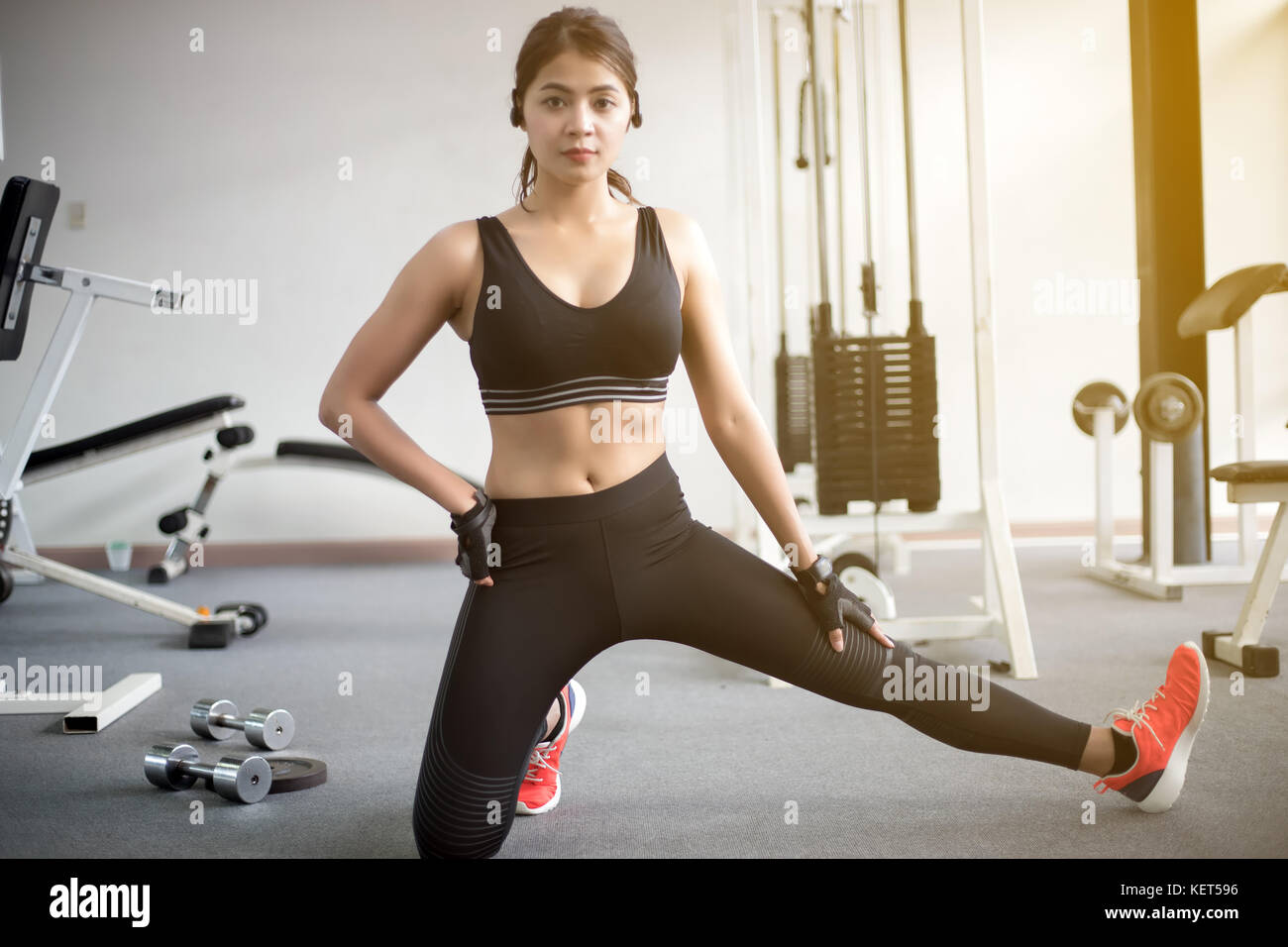 Blurry of beautiful muscular fit woman exercising building muscles and fitness woman doing exercises in the gym. - Stock Image