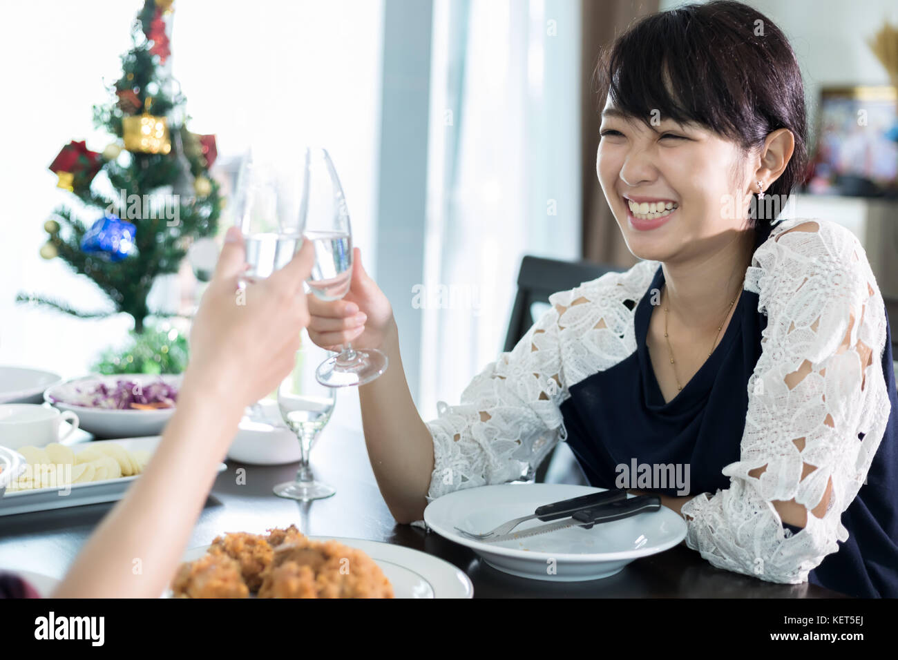 Asian young couple enjoying a romantic dinner  evening drinks while sitting at the dinning table on the kitchen - Stock Image