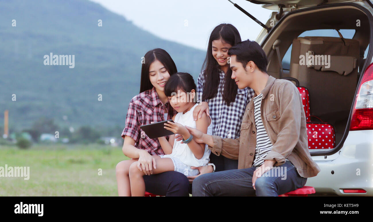 happy little girl playing ukulele with asian family sitting in the car for enjoying road trip and summer vacation,soft Stock Photo