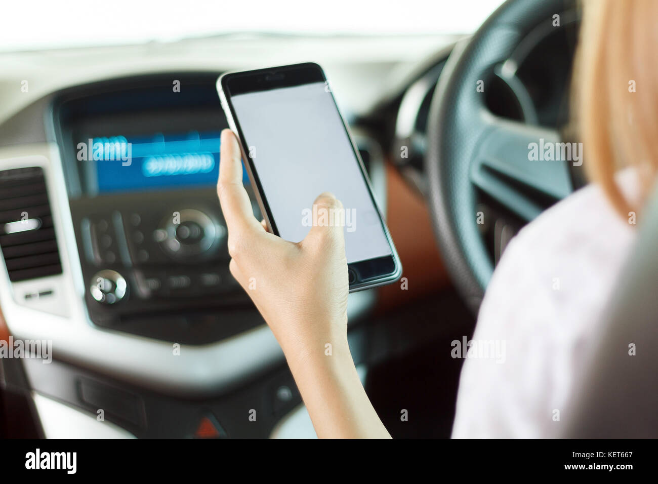woman asian  holding phone in car - Stock Image