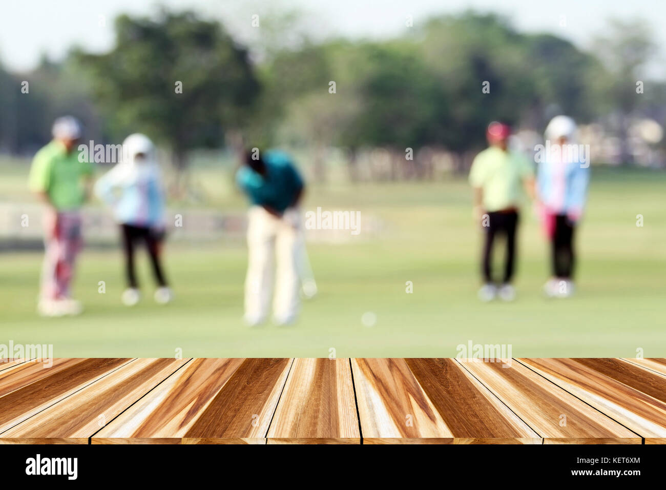 perspective wood and blurred golfers hit sweeping and keep golf course in the summer for relax time - Stock Image