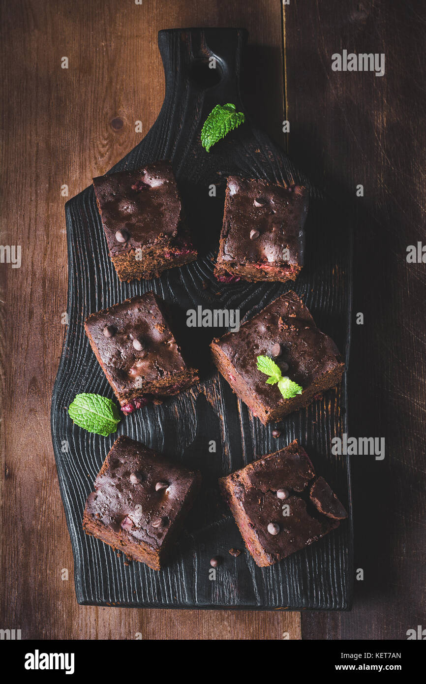 Dark chocolate brownies decorated with mint leaf on dark background. Top view, vertical composition - Stock Image