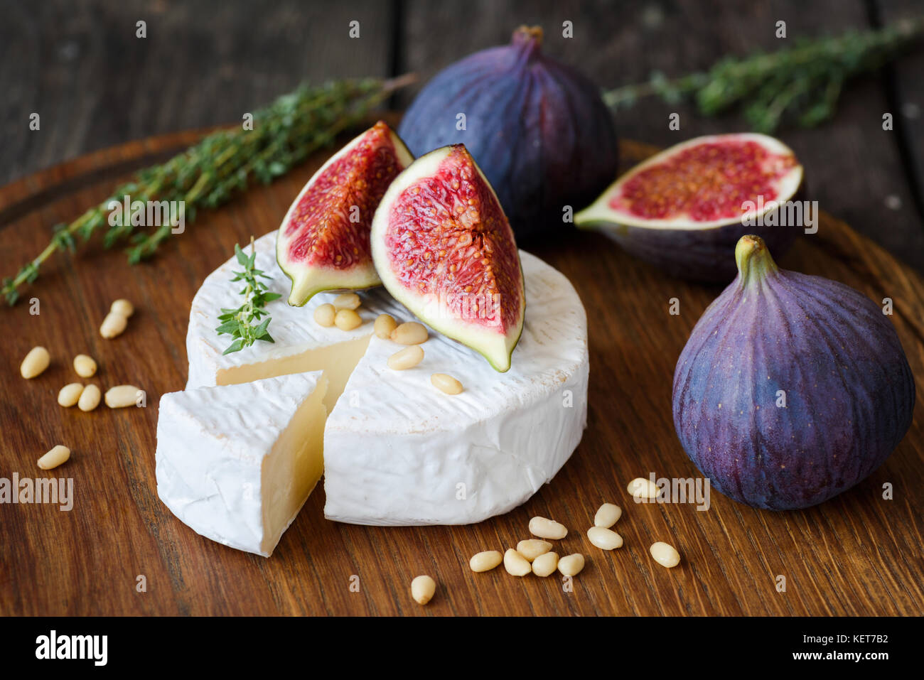 Camembert cheese with fresh purple figs, thyme and pine nuts on cutting board - Stock Image