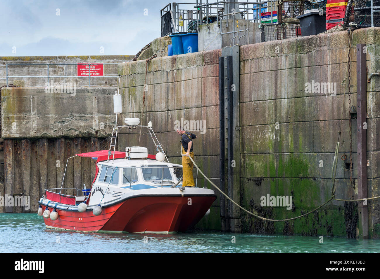 Newquay Harbour Cornwall - a boat being tied up at the quay at Newquay Harbour. - Stock Image