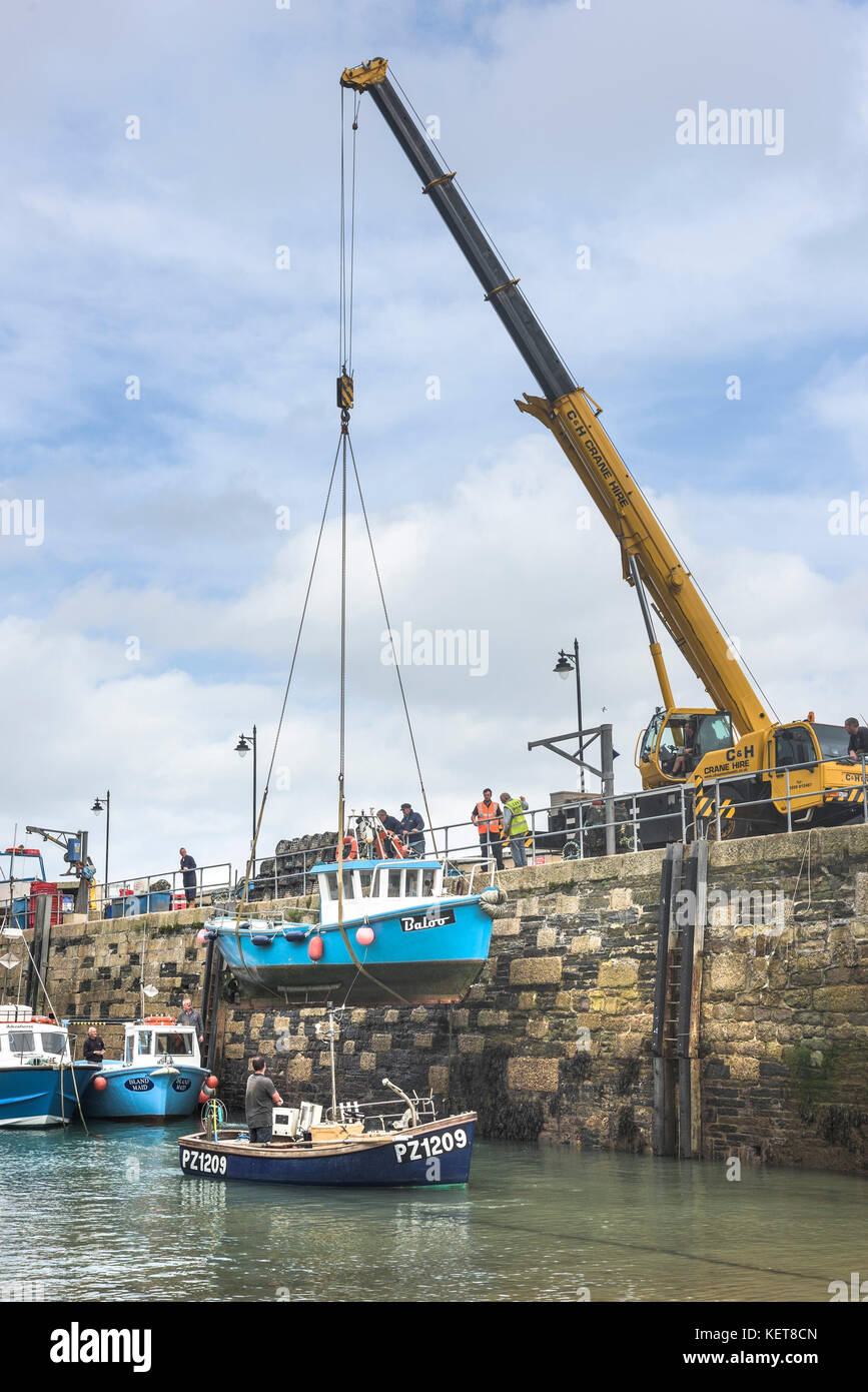 Newquay Harbour Cornwall - a boat being craned out of Newquay harbour for Winter storage. - Stock Image