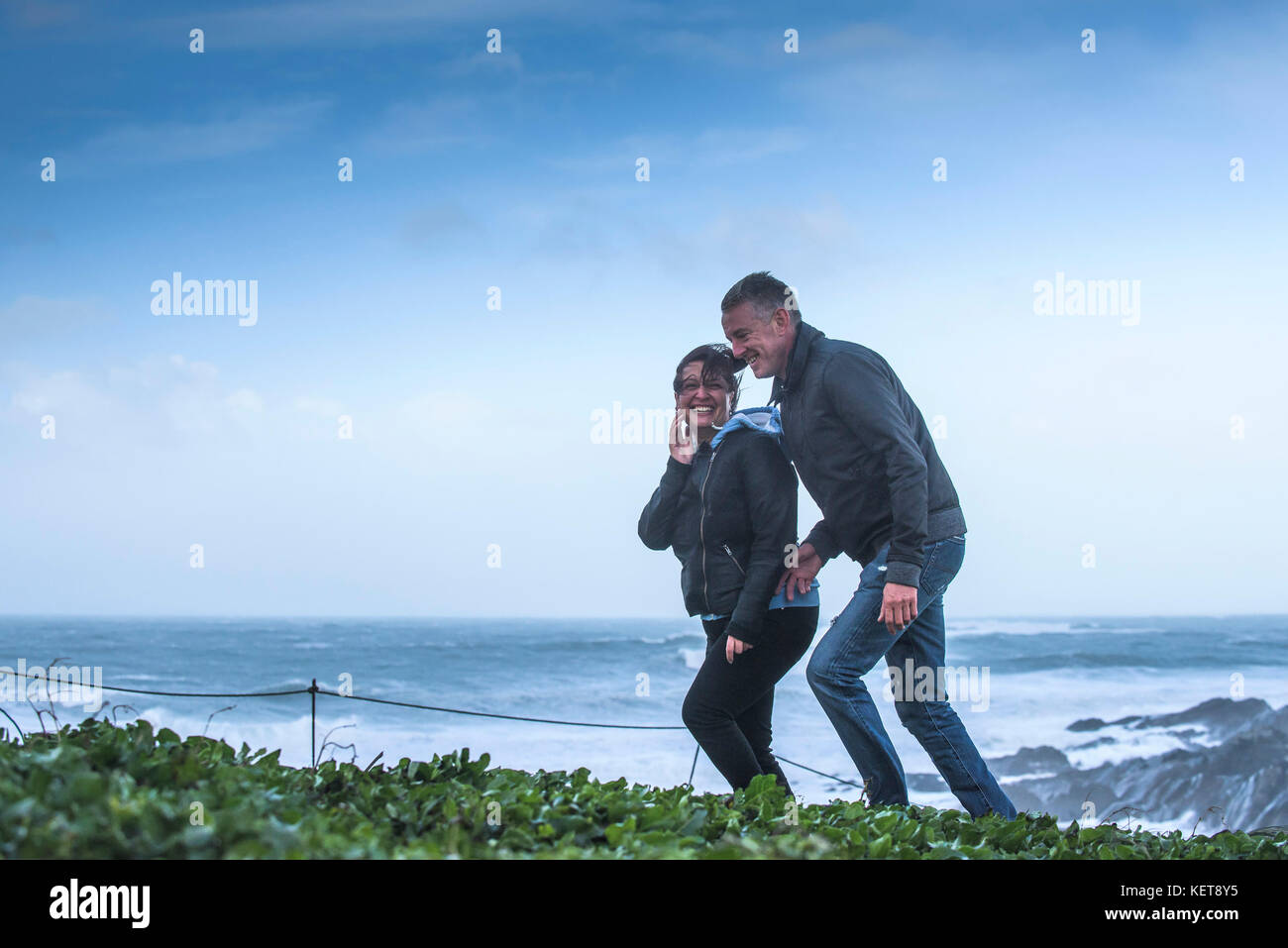 UK Weather Storm Brian - a couple laughing and enjoying walking in stormforce winds as Storm Brian brings severe - Stock Image