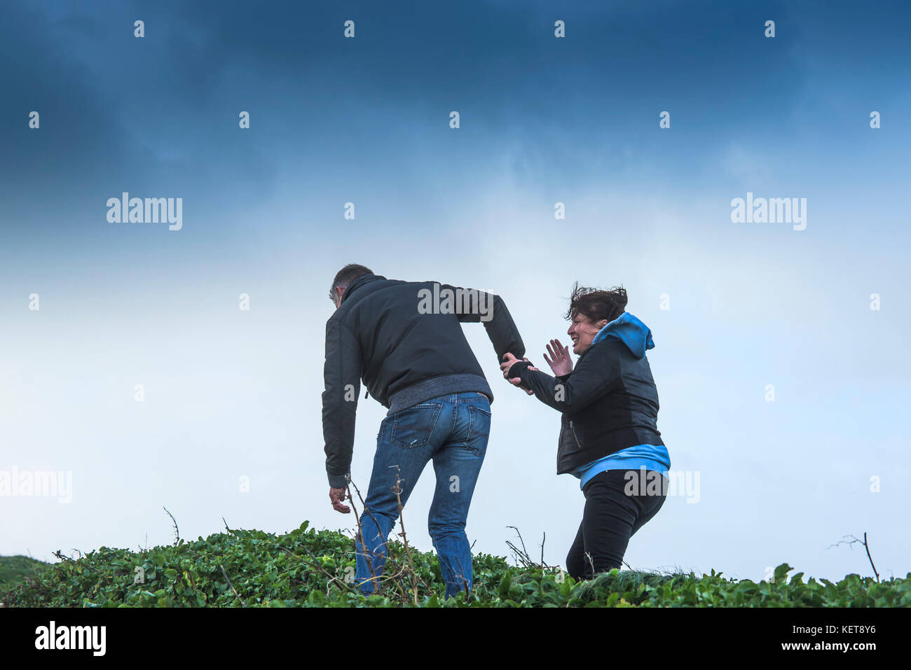 UK Weather Storm Brian - a couple enjoying walking in stormforce winds as Storm Brian brings severe weather to the - Stock Image