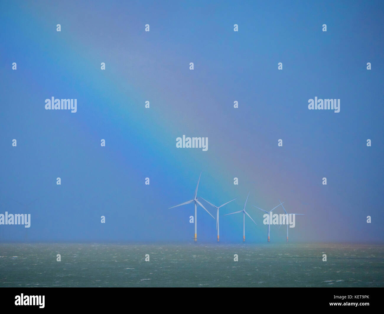 Rainbow over a wind turbine farm off shore at Whitstable Kent UK - Stock Image