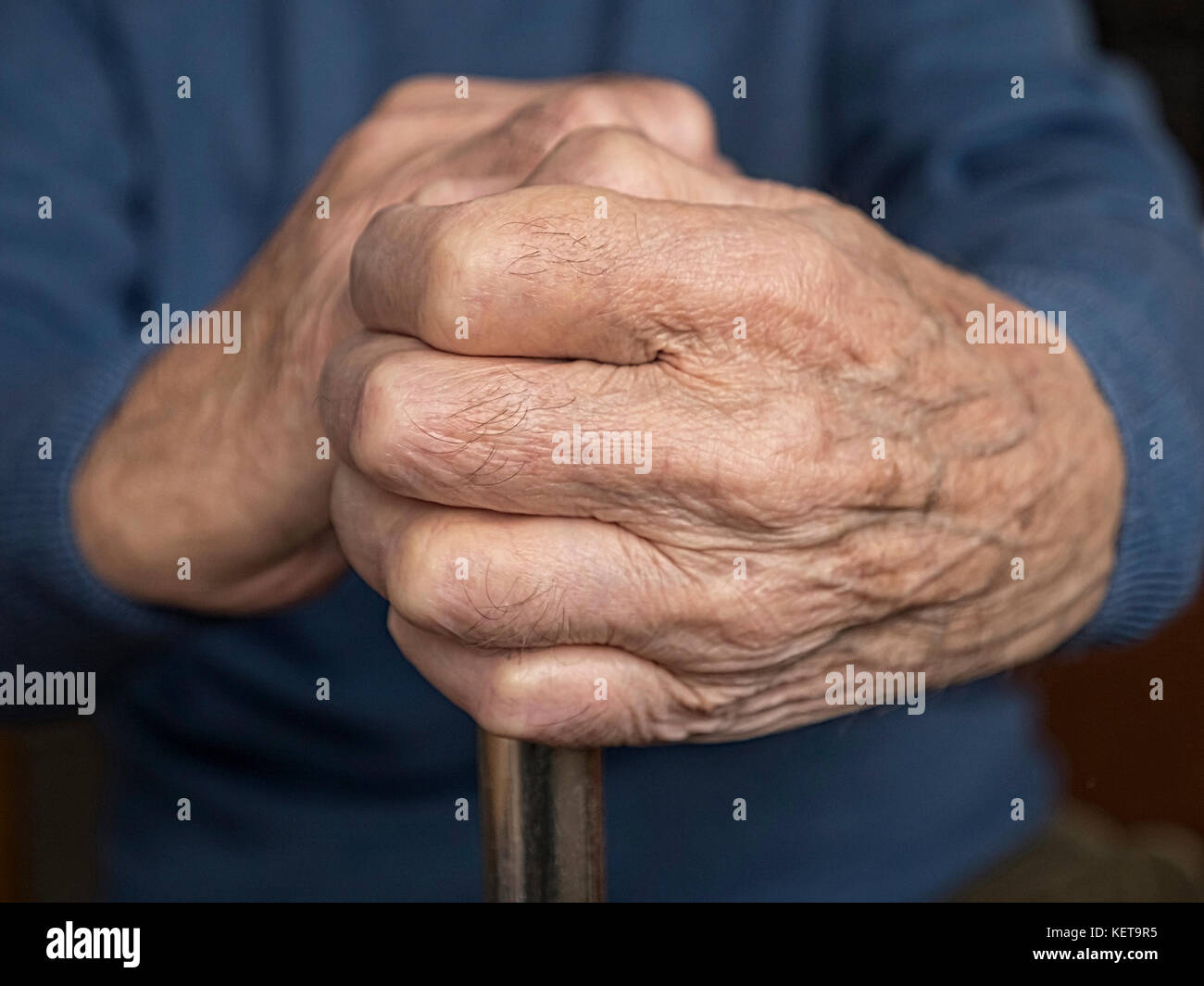 Old mans hands resting on walking stick. - Stock Image