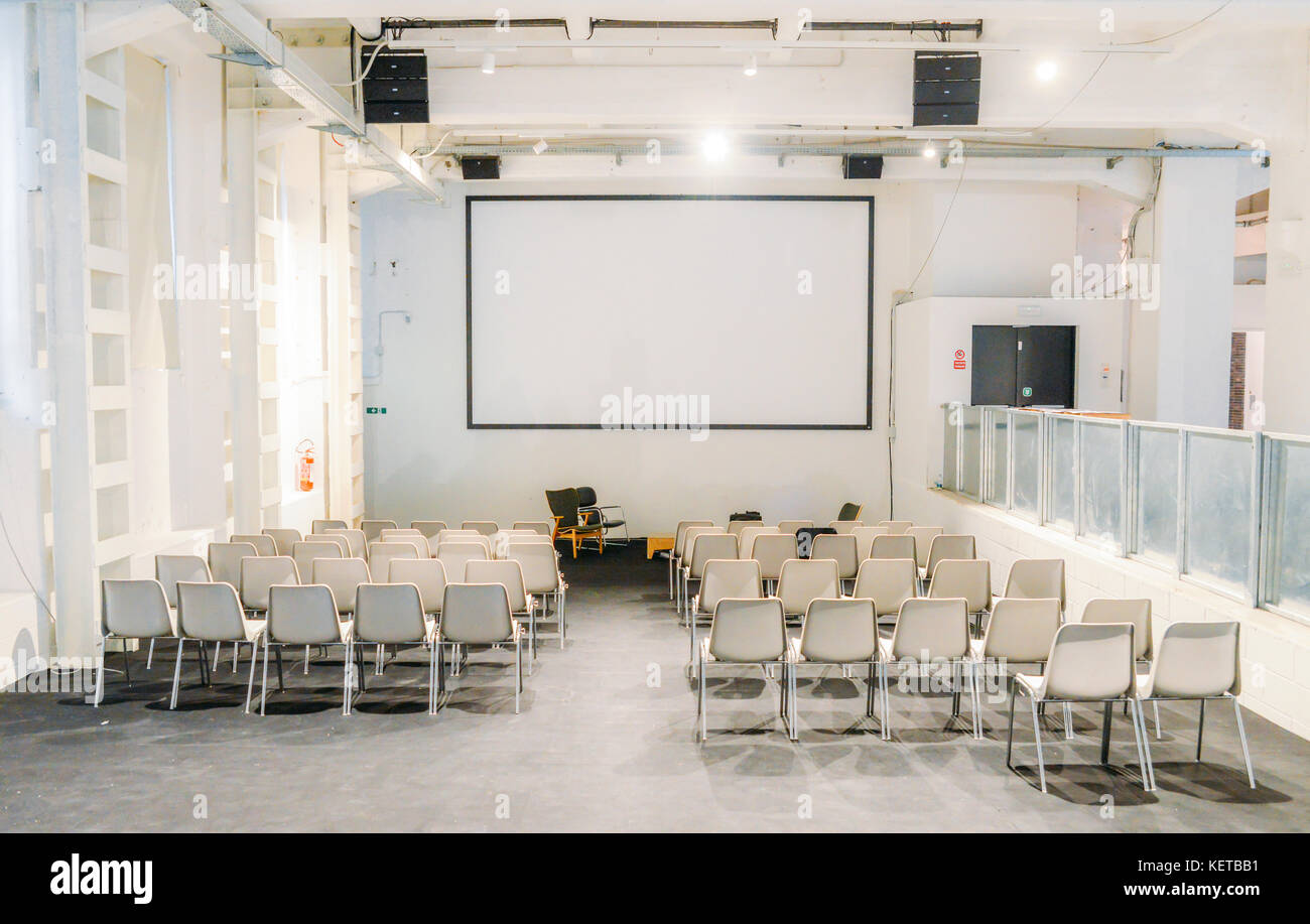 Empty and brightly lit presentation room with chairs and projector - Stock Image