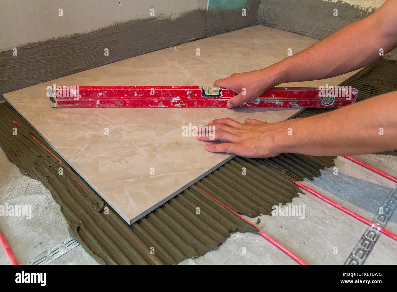Workers hands with ceramic tiles and tools for tiler floor tiles workers hands with ceramic tiles and tools for tiler floor tiles installation home improvement renovation ceramic tile floor adhesive mortar le dailygadgetfo Images