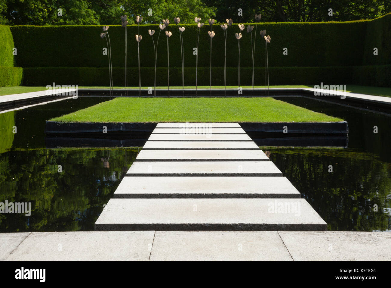 The contemporary Water Garden with modern art sculpture is enclosed by high yew hedges, Kiftsgate Court gardens, - Stock Image