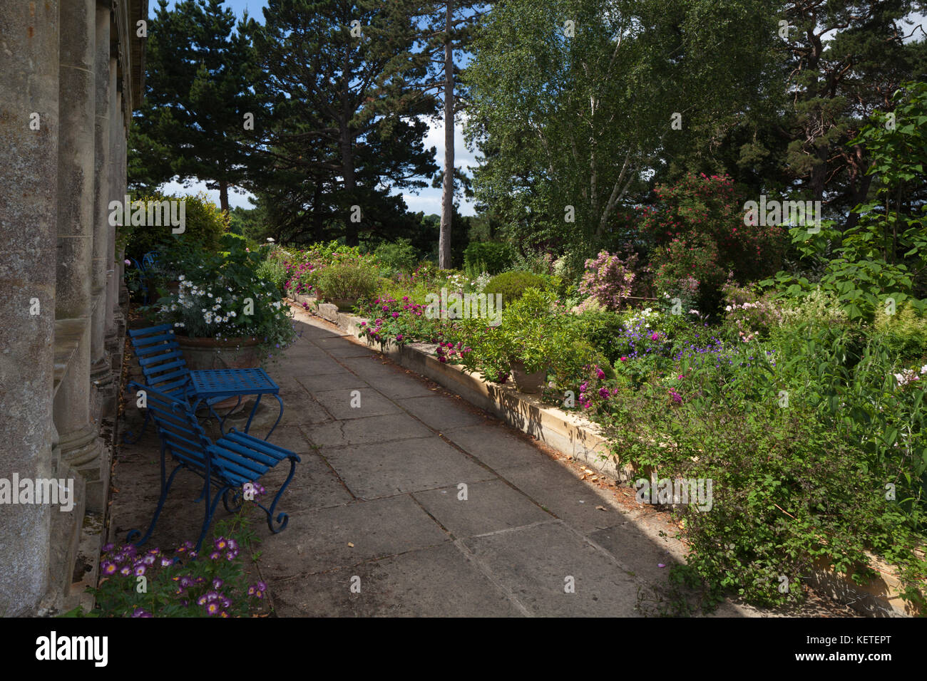 Blue table and chairs on the terrace overlooking the wide border of Kiftsgate Court near Chipping Campden, Cotswolds, - Stock Image