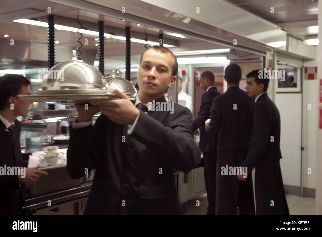 Europe-France-Paris-Plaza-Athene-Restaurant Aain Ducasse. The waiters coming out of the Kitchen - Stock Image