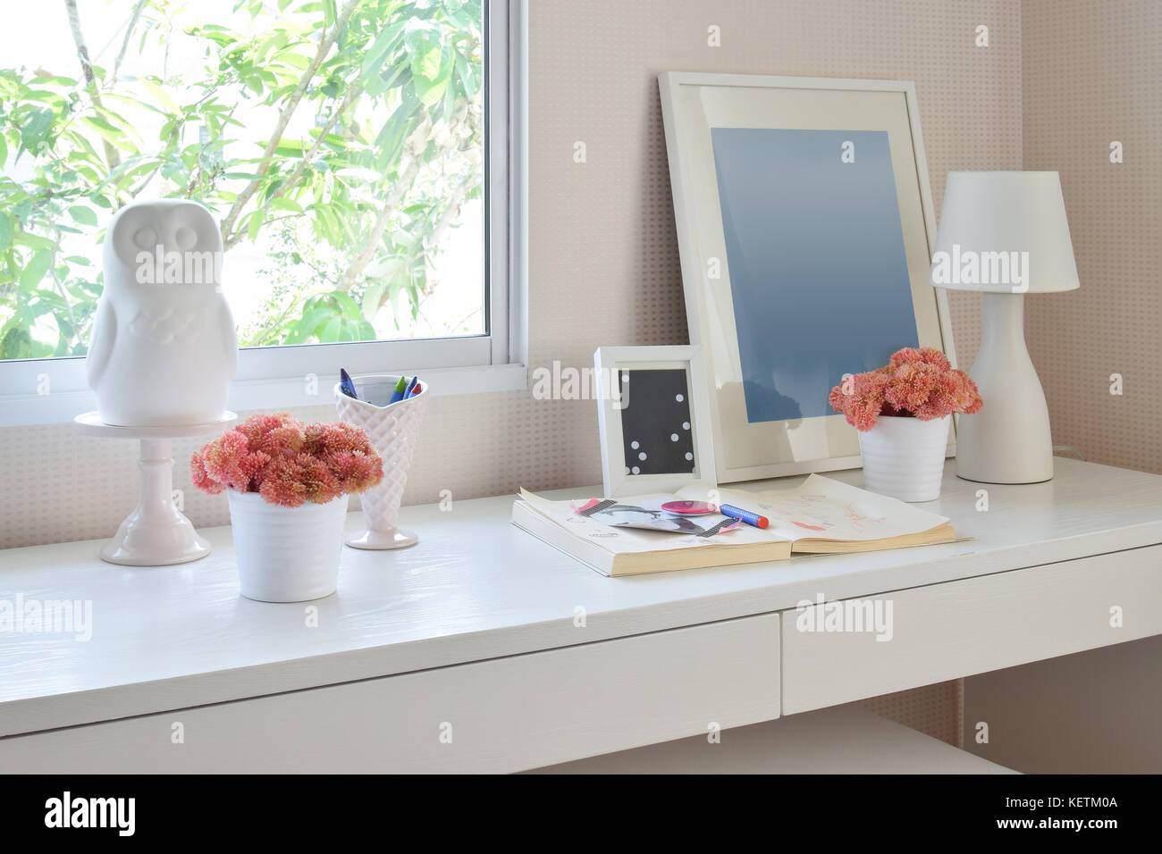 color pencils and sketchbook on wooden table in kids room - Stock Image
