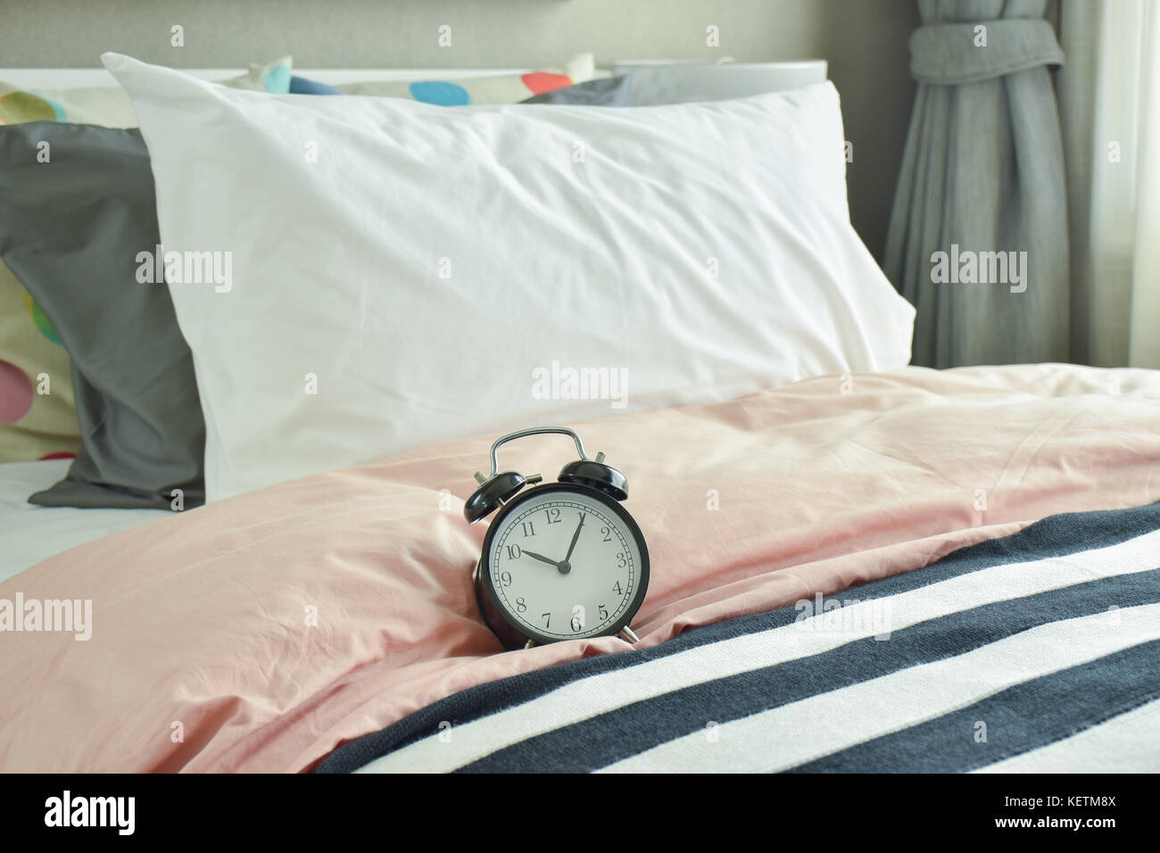 Black Alarm Clock On Bed With Colorful Bedding Stock Photo Alamy