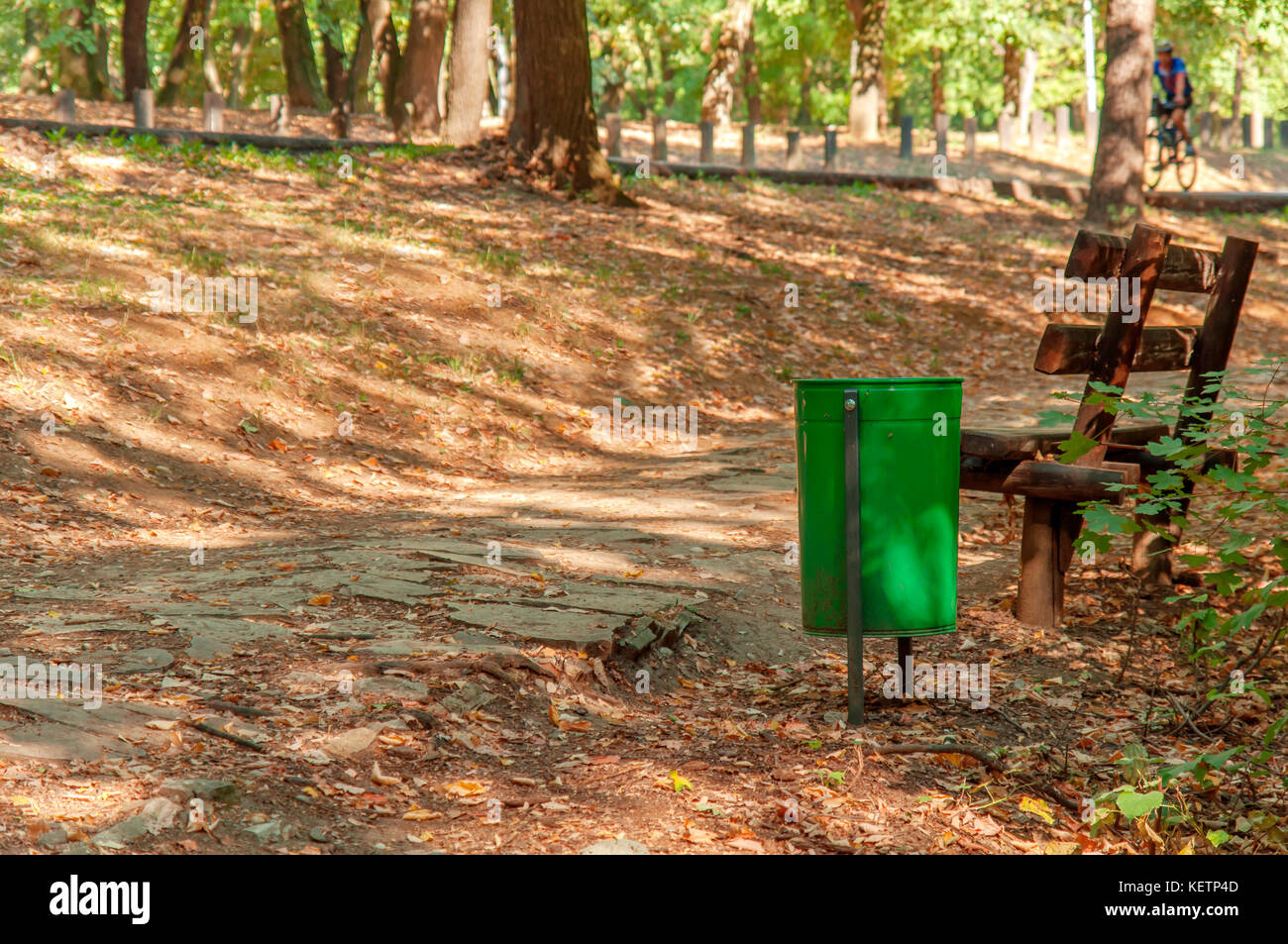 Trash can in forest with pathway for walking an running - Stock Image