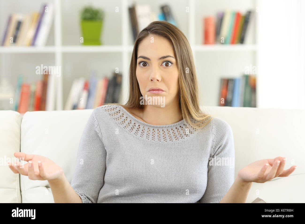 Front view of a doubtful woman shrugging shoulders and looking at you sitting on a sofa at home - Stock Image