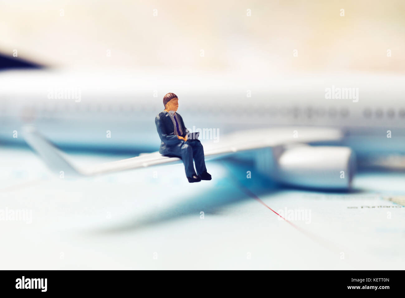 business travel concept - businessman sitting on a plane wing and working with laptop - Stock Image