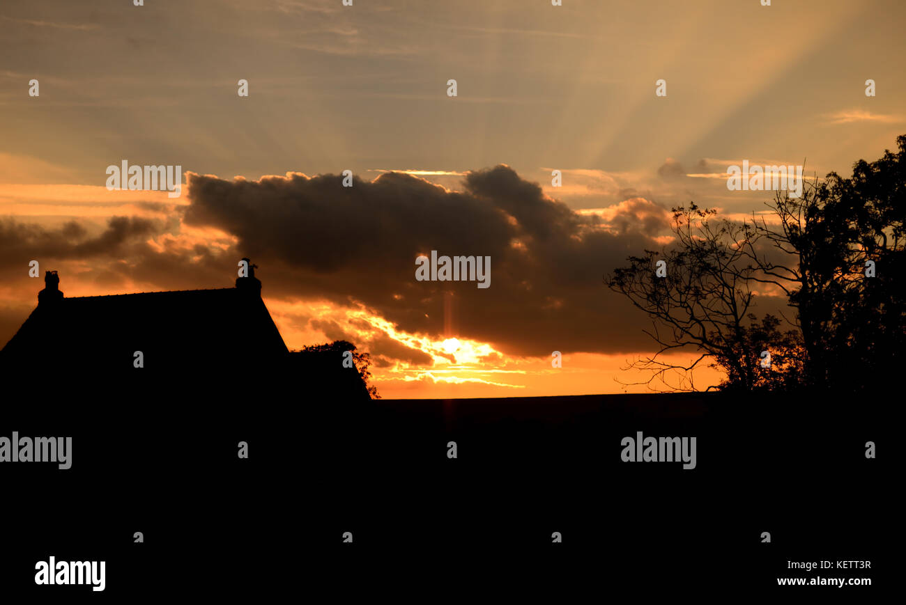 A house silhouetted against the sun setting over the North York Moors. - Stock Image