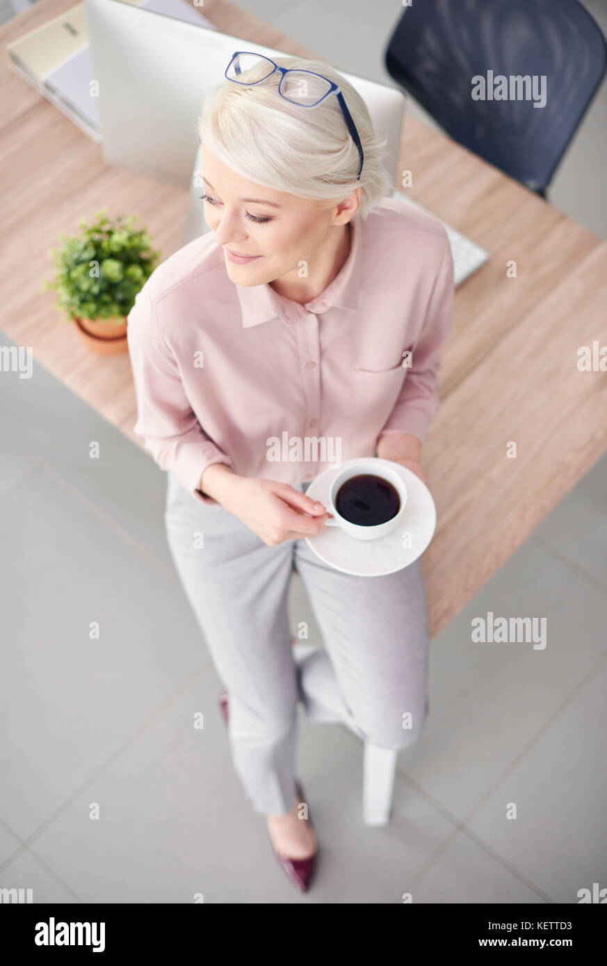 Smart business person with coffee sitting at desk - Stock Image