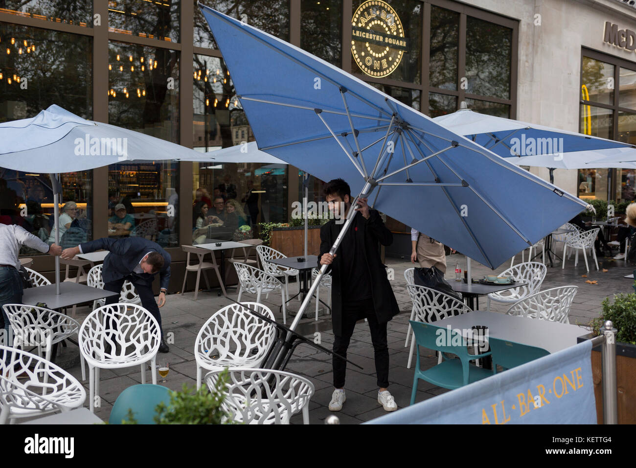 Bar customers straighten large umbrellas just blown over during a