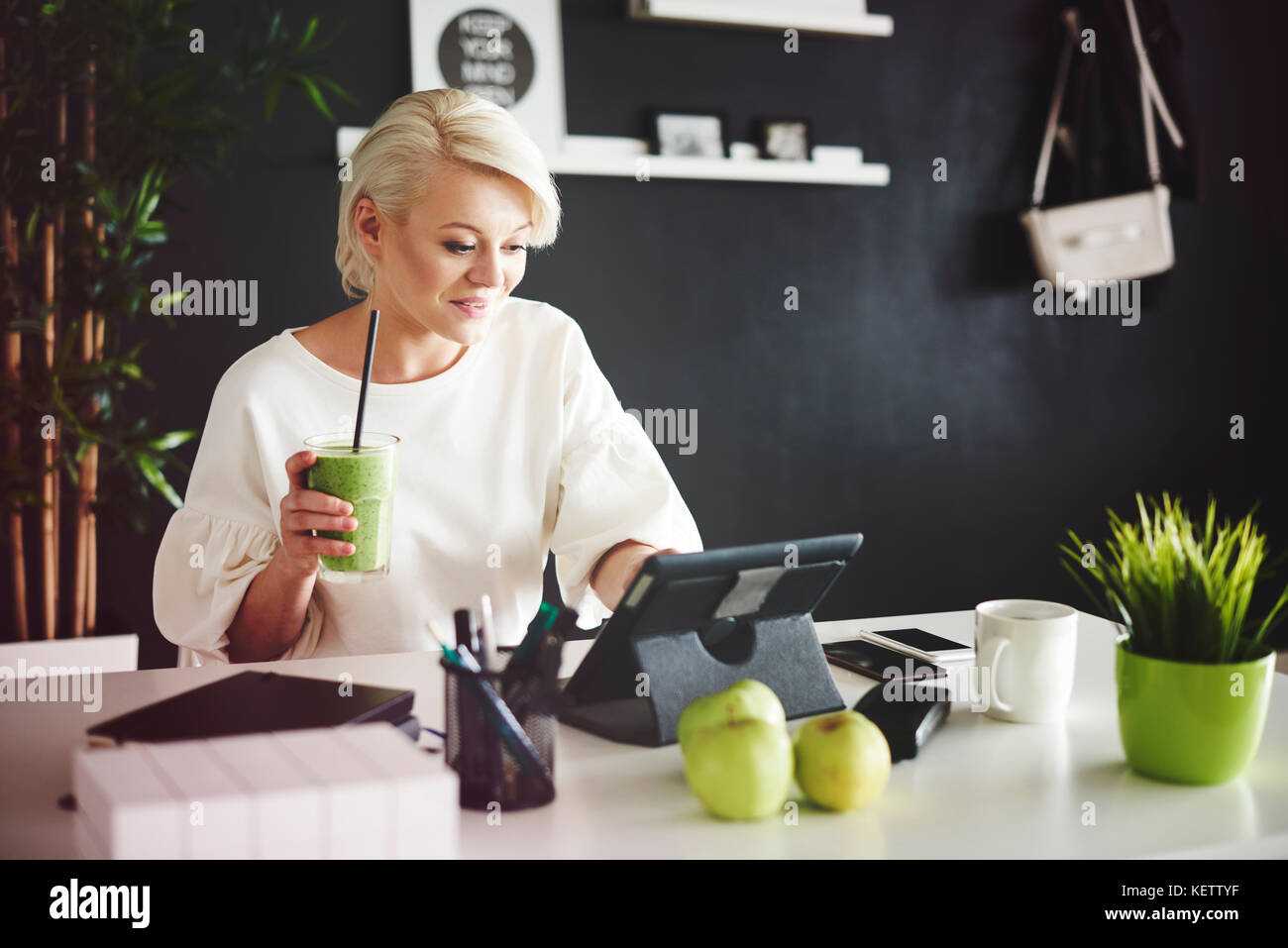 Woman with smoothie using a digital tablet at her desk - Stock Image