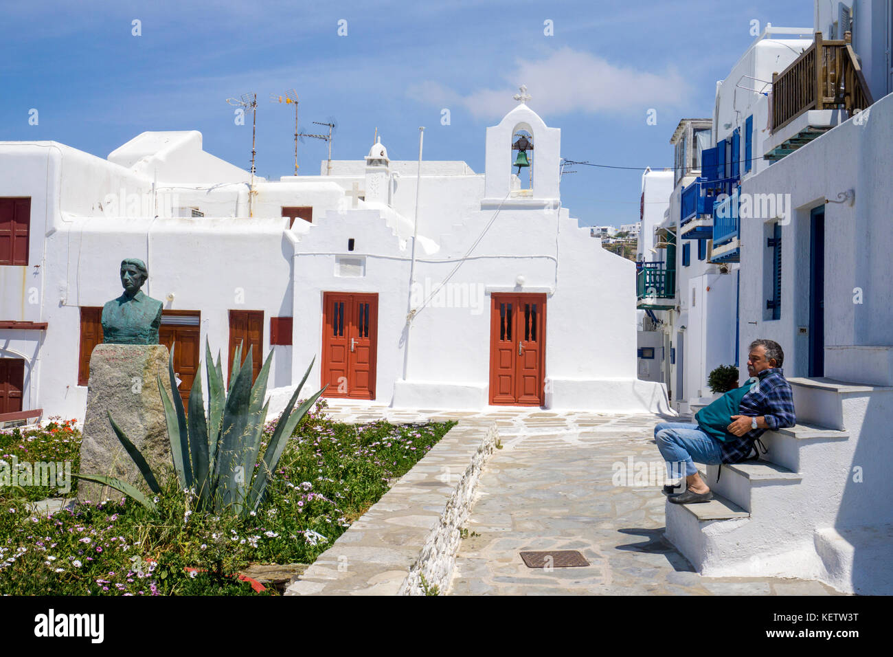Greek man sitting on stairway at a chapel, Mykonos-town, Mykonos, Greece - Stock Image